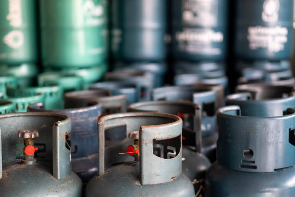 A collection of blue and green propane gas cyclinders tagged and filled for use