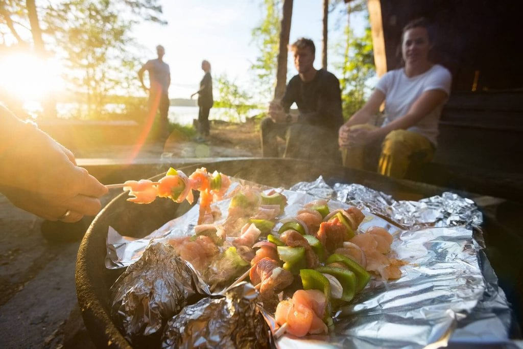 A group of hungry campers watch as their dinner cooks in foil on campfire