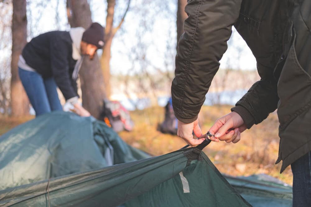 A pair of campers adjust olive rain fly tarp to cover tent