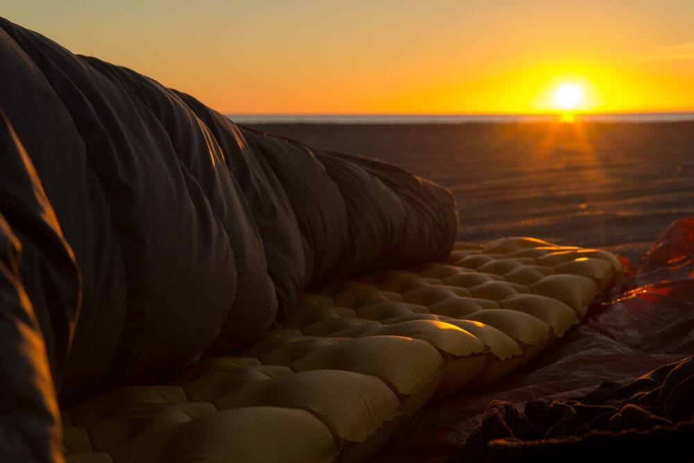 Adventurer on the beach in sleeping bag laying on air mattress