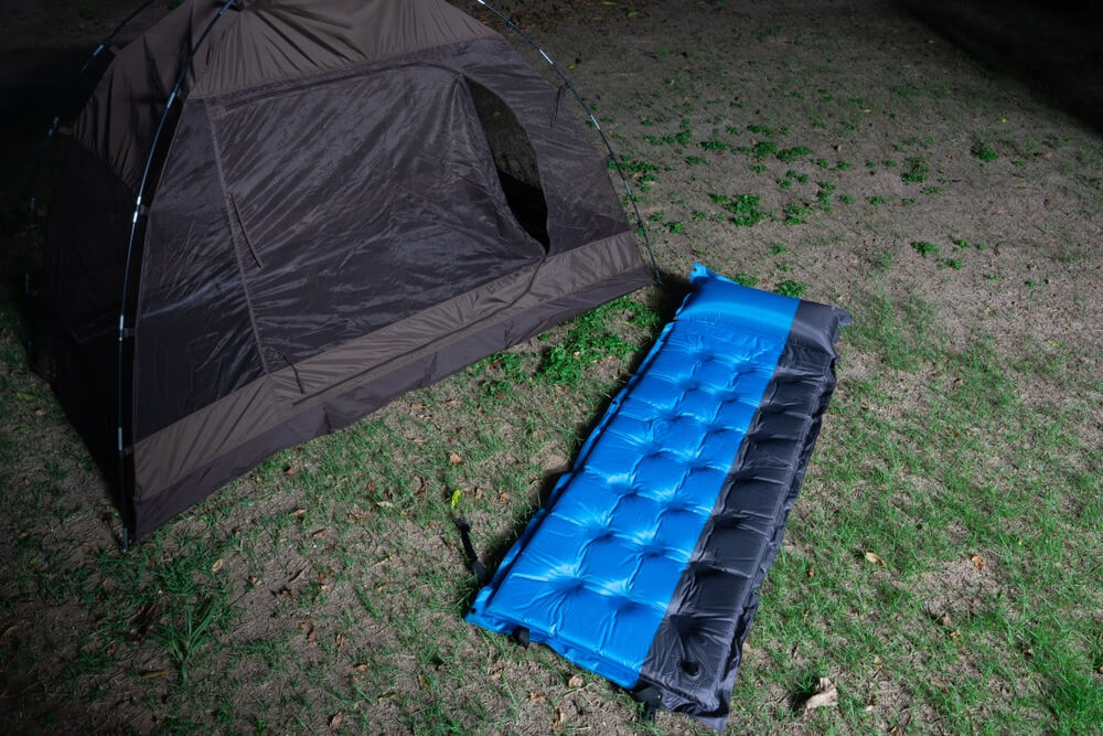 A repaired blue and black air mattress outside on grass in night ready for tent
