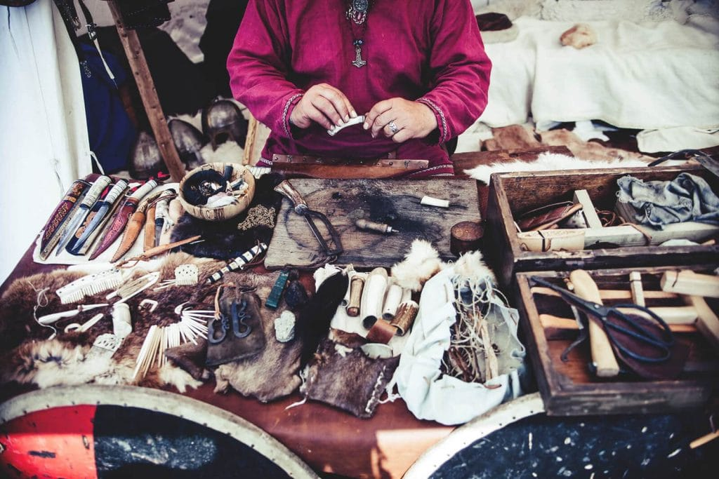 Awl for leather stiching in front of lady with many other goods for sale