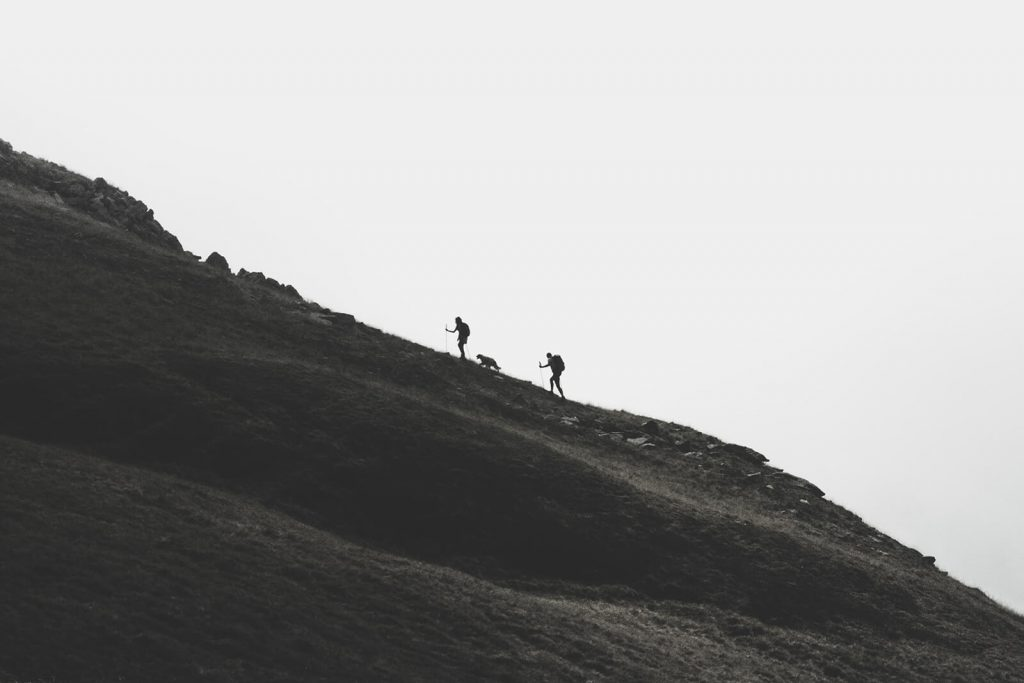 Black and white silhouette two hikers with dog on steep hill