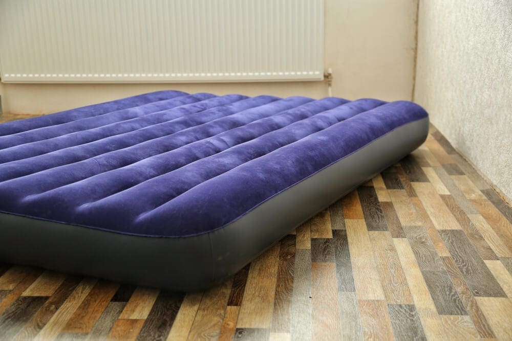 Blue air mattress lying directly on a timber floor