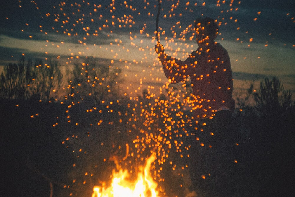 Afternoon lone camper throws log on fire creating sparks and flying embers