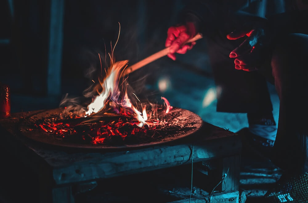 How hot is a campfire, A long camper sits in front of a camp fire at night that has various glowing colours