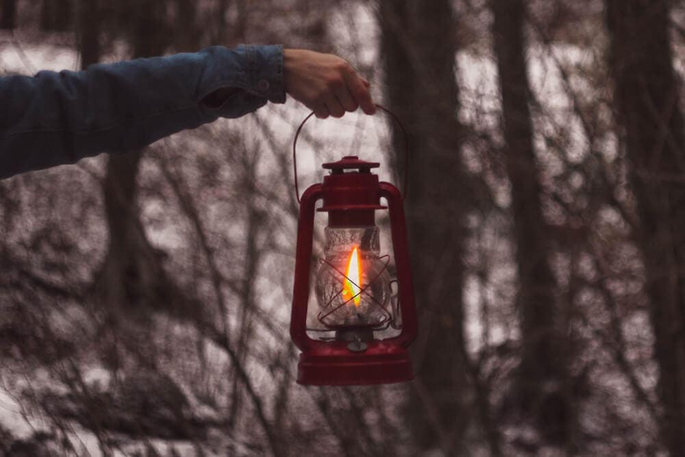 Camper using fuel latern at dusk in snowy wooded area