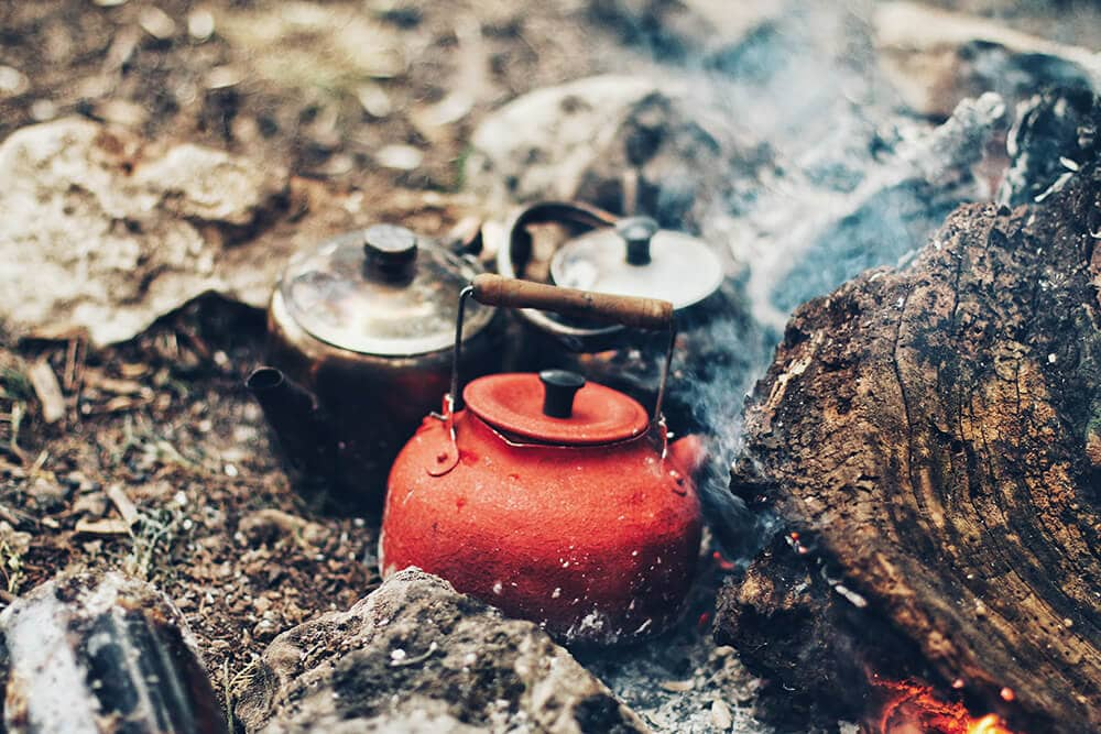 Coffee is brewing early morning on the campfire red and black pot