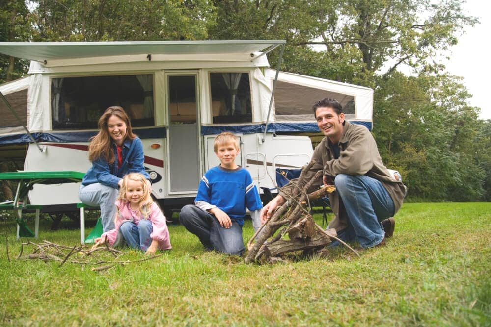 Family builds campfire infront of pop up trailer
