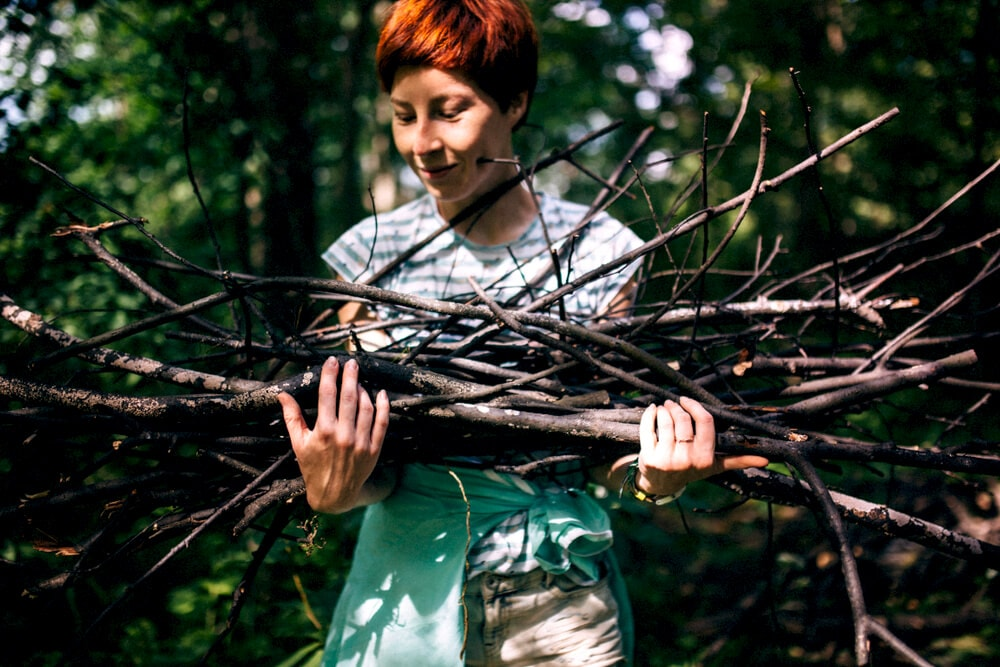 Female camper collecting an arm full of firewood