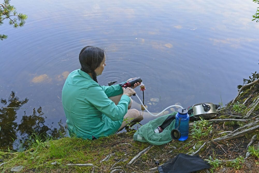 Female hiker takes a break on the edge of lake to filter water using portable pump filter