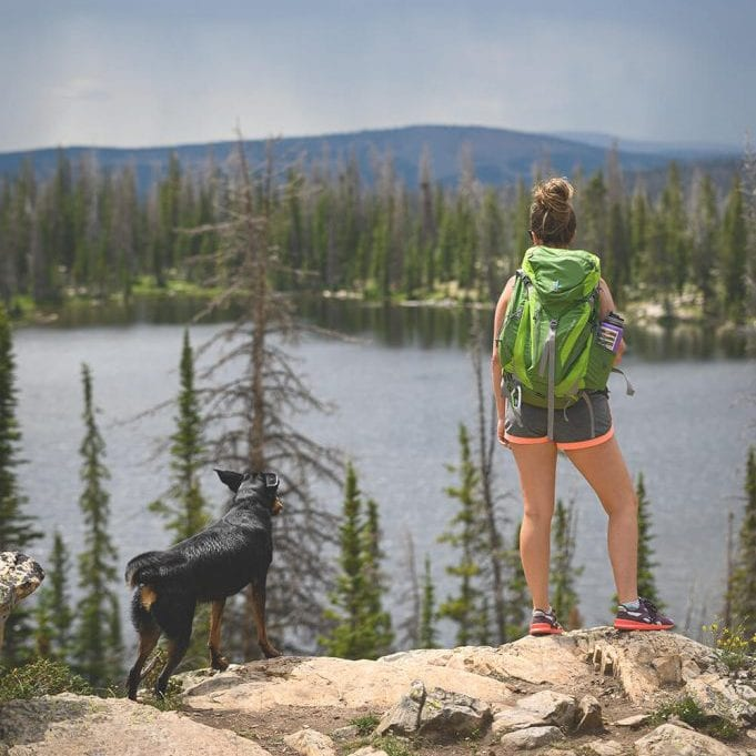 Female hiker with dog taking rest looking out onto water on trail hike