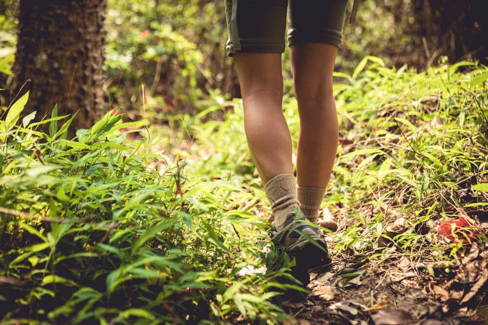 Female hiker with sock liners hiking in spring backcountry