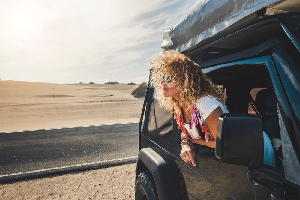 Female with blond curly hair stops driving and leans out of black jeep towards desert landscape in day