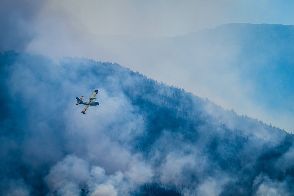 A yellow emergency plane flies over a mountain of bushfires to eject water attempting to extinguish