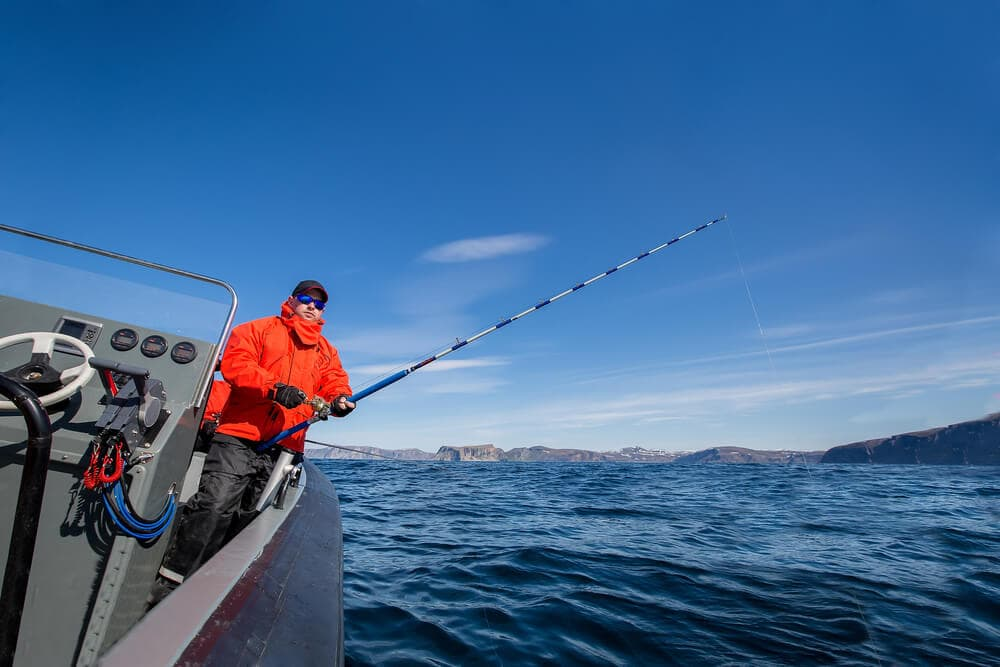 Hi-visible-fisher-with-saltwater-spinning-reel-on-boat-fishing