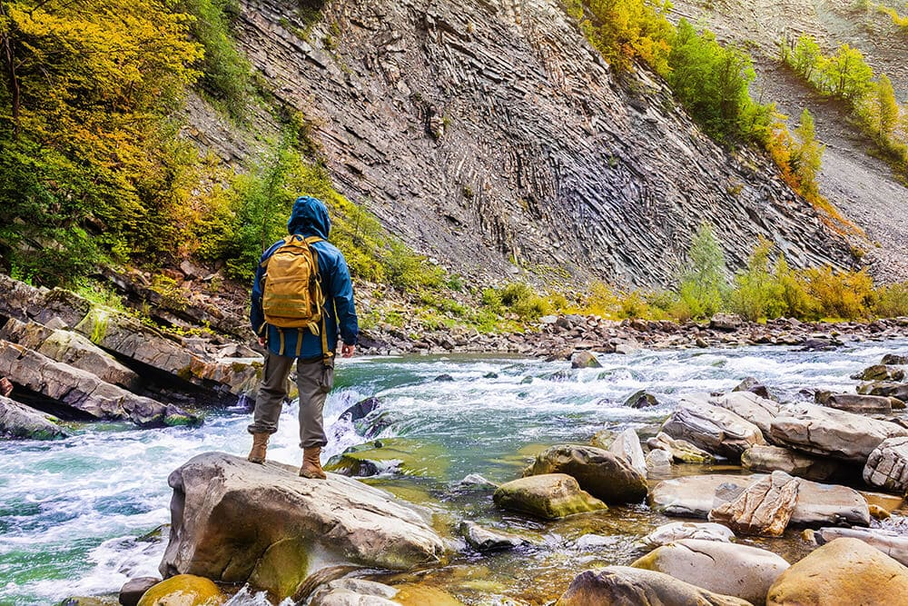 Hiker with backpack lots of pockets sightseeing flowing riverx