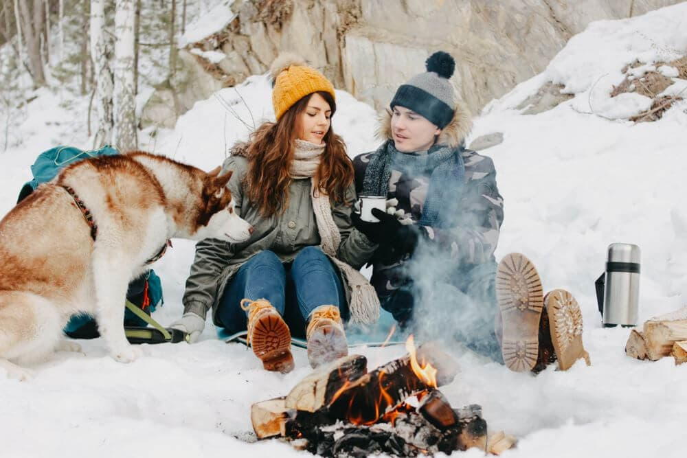 Husky and family in snow around a campfire cold camping
