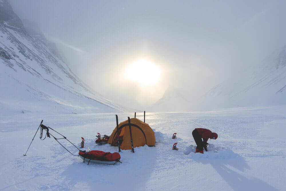 Lone-camper-establishes-basecamp-on-flat-surface-in-extreme-snow-conditions-