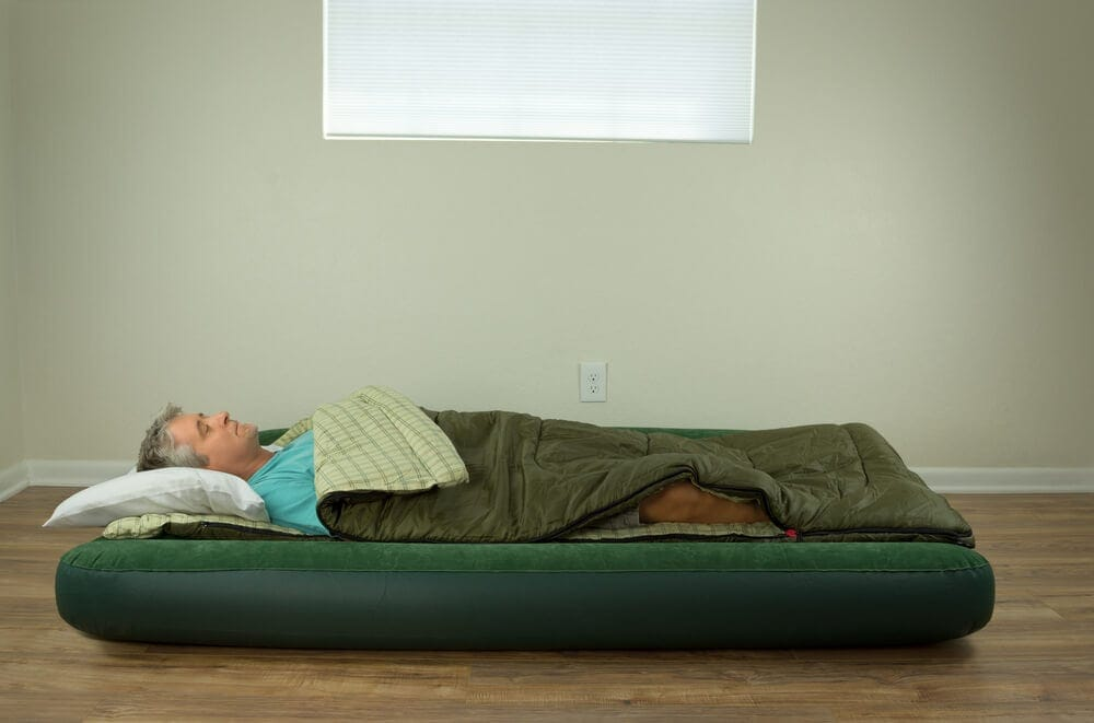 Man lying directly on mattress on floor without support frame