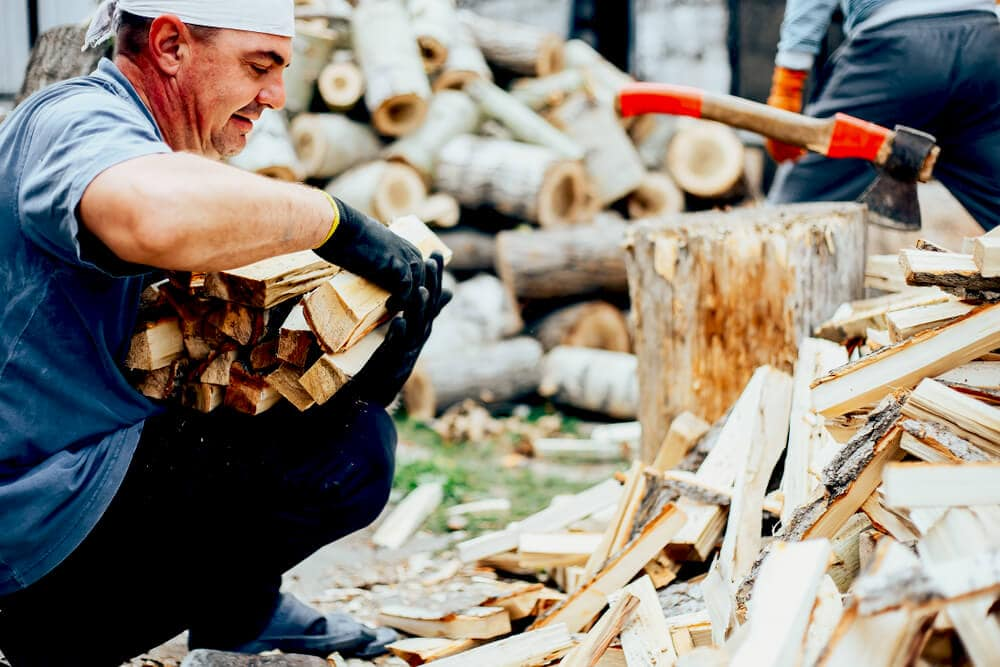Older man crouching down collecting firewood
