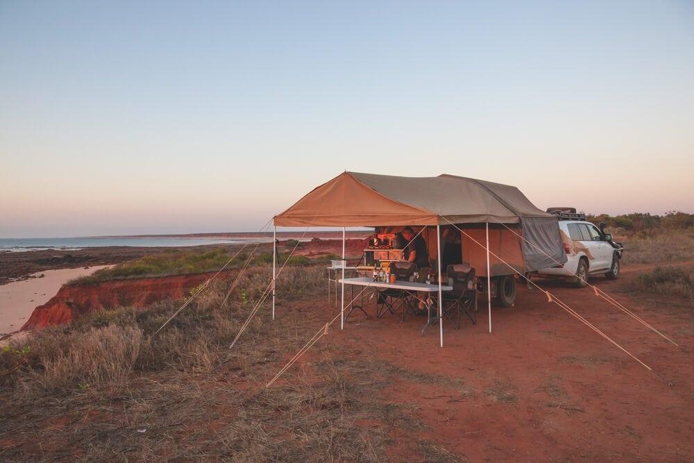 Outback camper prepares meal under pop up camper trailer