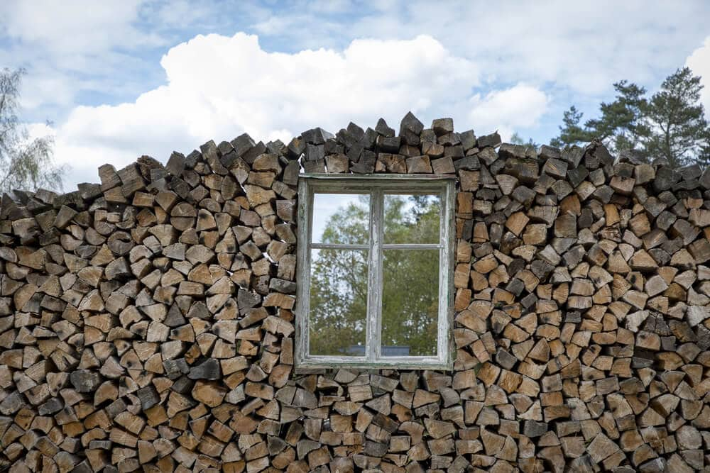 Shed constructed from firewood with single window