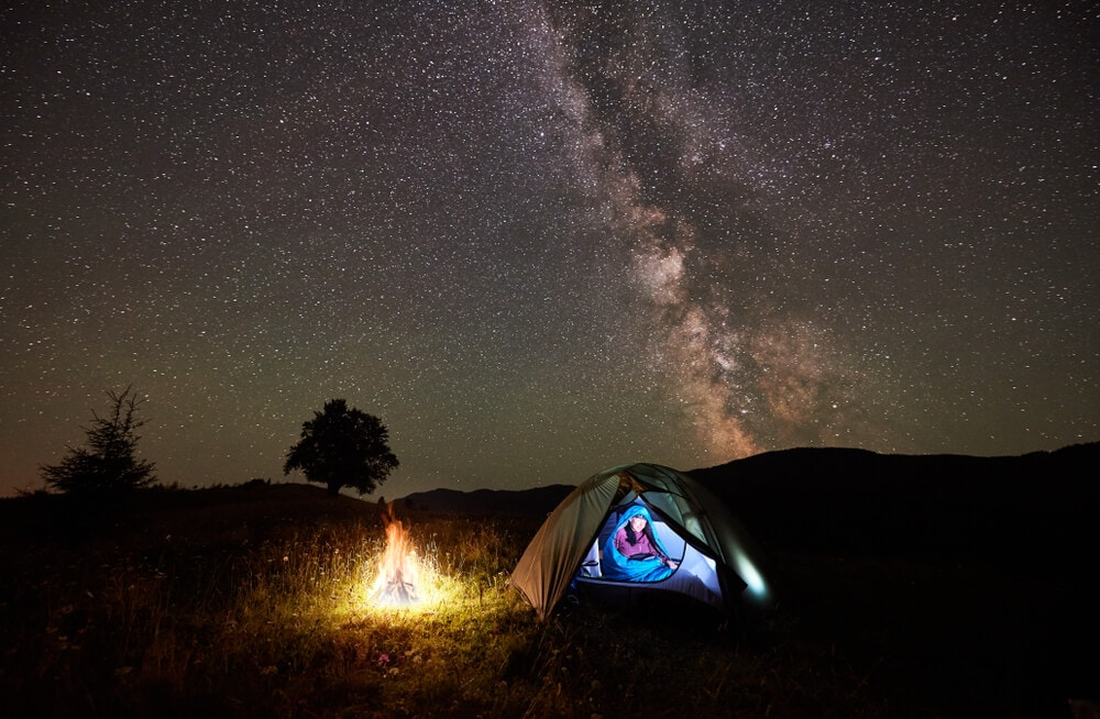 Single-female-camper-in-blue-tent-next-to-campfire-relaxes-at-night-with-sky-full-of-stars