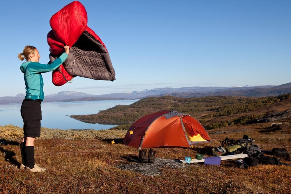 Solo female camper dusts off sleepingbag at base camp near lake and red tent