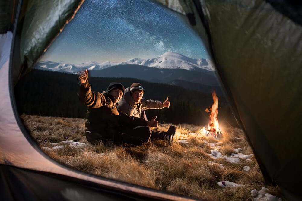 Two friends camping in winter outside white capped mountaines with tent