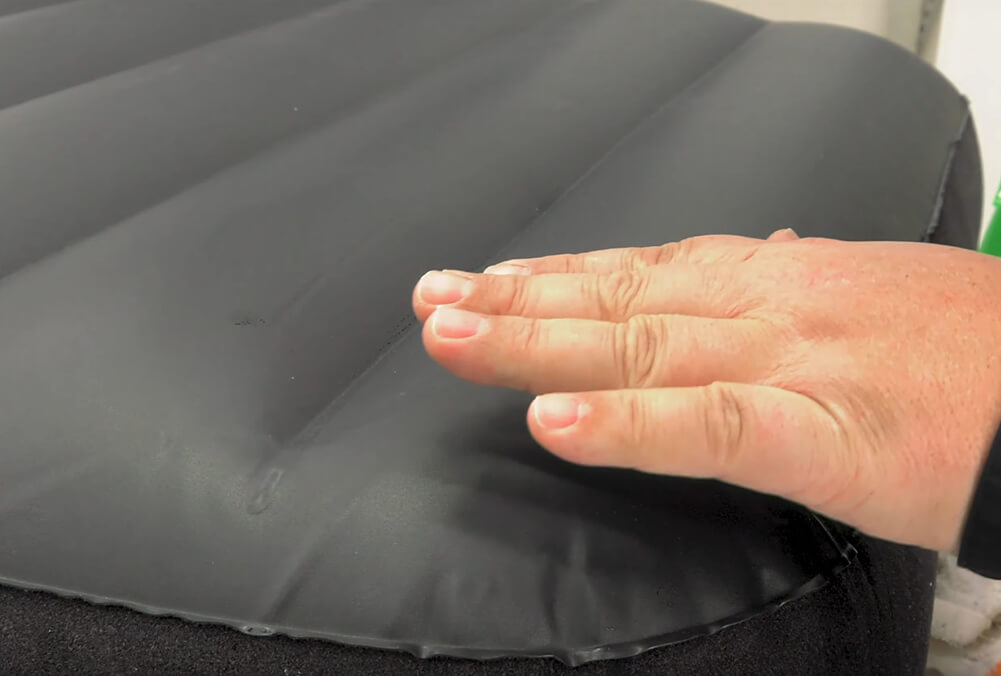 Pressing and feeling with hand for escaping air to find air mattress holes
