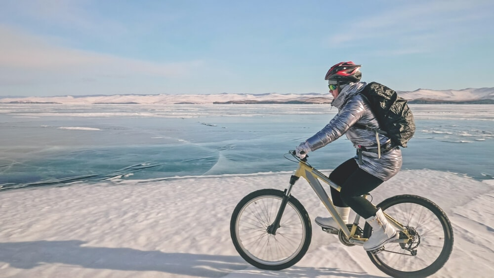 Winter cyclist wears a polyester jacket to protect their core from wind chill