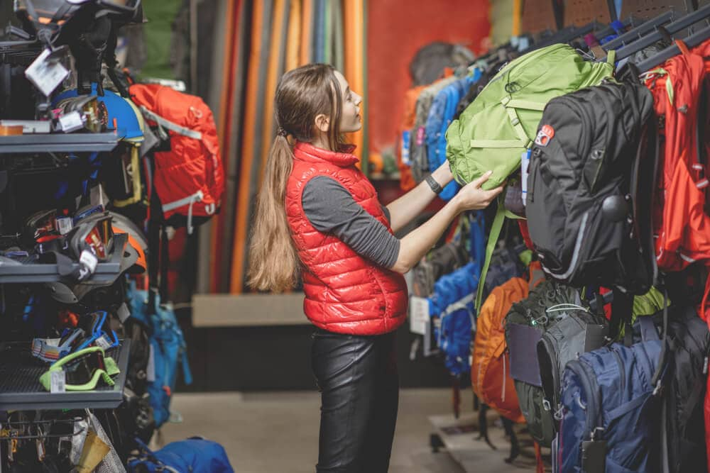Young female shopping for camping gear inside store examines green backpack